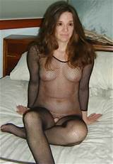 Shy MILF wearing a black see-through fishnet outfit in bed ready to ...